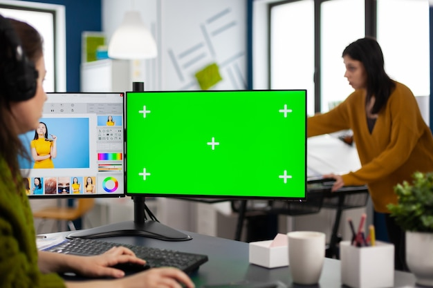 Fotoretusche-bearbeitung von assets im digitalen retuschierprogramm, farbkorrektur des kundenbildes, arbeiten im produktionsstudio mit blick auf computer mit grünem bildschirm, chroma-key-mockup-isolierte anzeige
