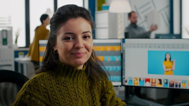 Fotoretusche sitzt am kreativen arbeitsplatz und schaut lächelnd in die kamera