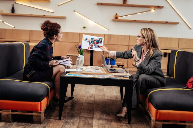Fotos zeigen. modedesignerin zeigt ihrer persönlichen assistentin, die vor ihr sitzt, fotos von neuen modellen
