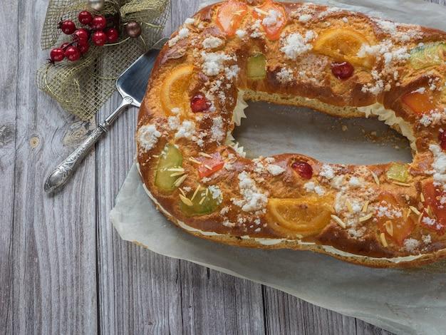 Fotoserie über die ausarbeitung des typisch spanischen desserts für das fest der könige im januar. spanischer weihnachtskuchen mit früchten, nüssen und zuckerguss. konzept der spanischen küche