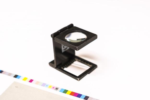 Fotosession bei einer offsetpresse. drucken in tinte mit cmyk, cyan, magenta, gelb und schwarz. grafik, offsetdruck. einstellwerkzeug an kontrollstreifen