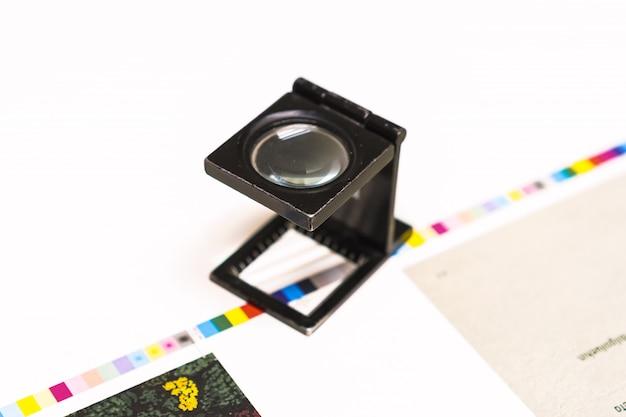 Fotosession bei einer offsetpresse. drucken in tinte mit cmyk, cyan, magenta, gelb und schwarz. grafik, offsetdruck. einstellwerkzeug für blattkontrollstreifen