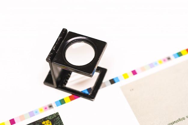 Fotosession bei einer offsetpresse. drucken in tinte mit cmyk, cyan, magenta, gelb und schwarz. grafik, offsetdruck. einstellwerkzeug für die fadenzählung