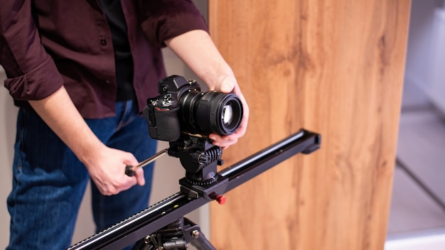 Fotosession zu hause. photograpger hält kamera auf der horizontalen leiste