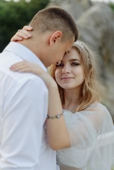Fotoshooting eines verliebten paares in den bergen. das mädchen ist wie eine braut in einem hochzeitskleid gekleidet.