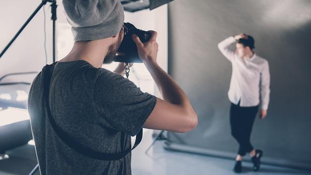 Fotoshooting mit mode. beruflicher beruf hobby. männliches model posiert im studio. sitzung hinter der bühne.
