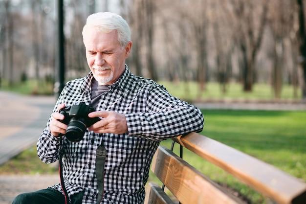 Fototechnik. erfreulicher reifer mann, der kamera benutzt und im park aufwirft