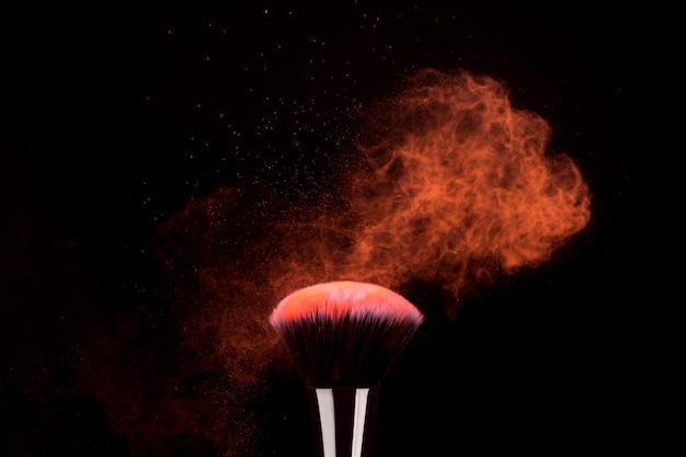 Foundation pinsel mit fliegenden partikeln aus hellem puder