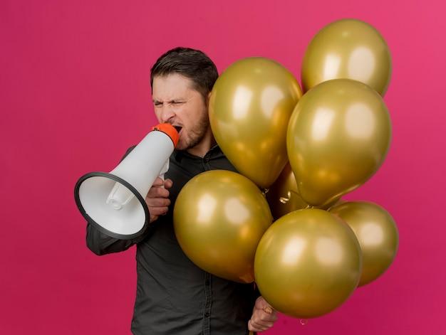 Foyful junger party-typ, der schwarzes hemd trägt, das luftballons hält und auf lautsprecher spricht, der auf rosa isoliert wird