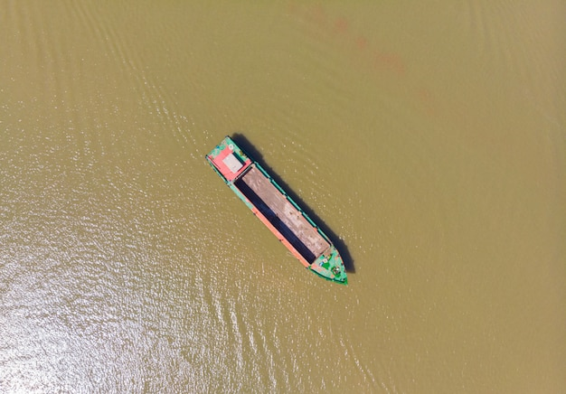 Frachtboot, das auf die mekong-delta-region, can tho, süd-vietnam schwimmt. direkt über dem top-down-wasserfahrzeug auf braunem, schlammigem wasser.