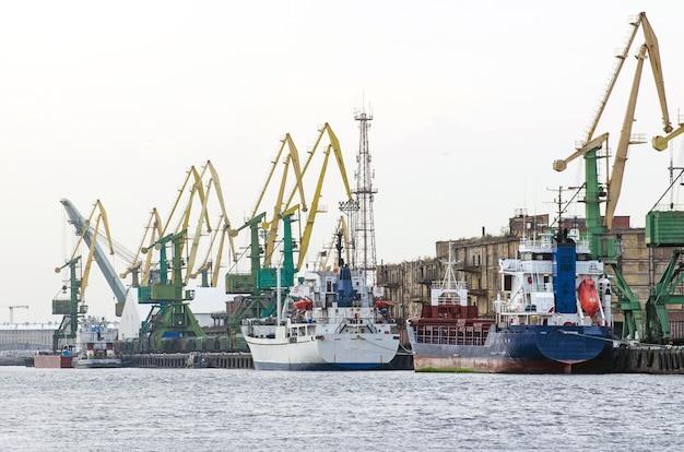 Frachtfrachtschiff und frachtcontainer arbeiten mit kran im hafenbereich