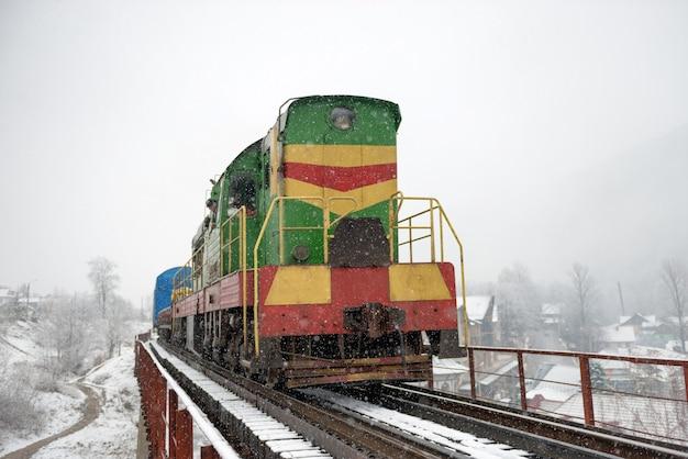 Frachtlokomotive auf der brücke in der nähe von winterwald mit bäumen im schnee