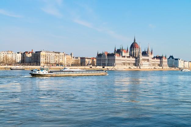 Frachtschiff fährt am parlamentsgebäude im zentrum von budapest vorbei