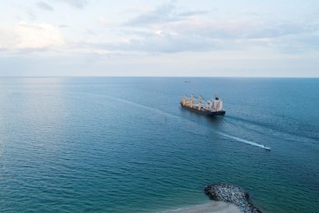 Frachtschiff im seeexport und -importkonzept binnenschifffrachtcontainer in der seefrachtlieferung