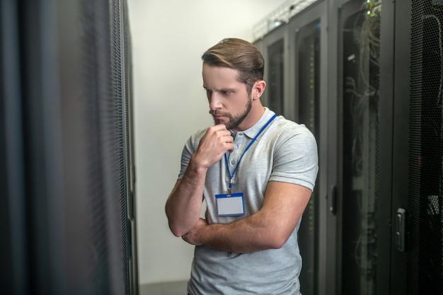 Frage. ernsthafter nachdenklicher junger erwachsener mann mit abzeichen, der im serverraum steht und die hand zum kinn berührt
