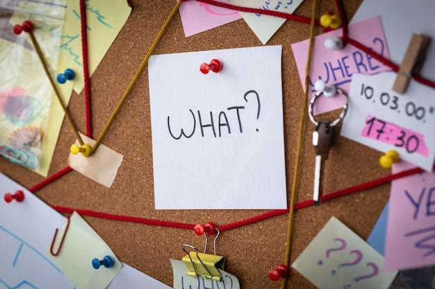 Frage. großaufnahme eines detektivvorstands mit beweis. in der mitte ist ein weißes blatt mit einem roten stift mit dem text was befestigt