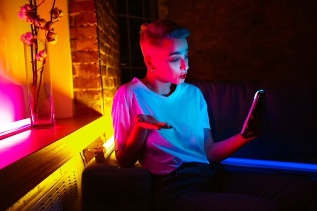 Fragen. filmporträt der stilvollen frau im neonbeleuchteten innenraum. getönt wie kinoeffekte, leuchtende neonfarben. kaukasisches modell mit smartphone in bunten lichtern drinnen. jugendkultur.