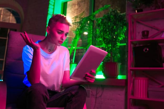 Fragen. filmporträt der stilvollen frau im neonbeleuchteten innenraum. getönt wie kinoeffekte, leuchtende neonfarben. kaukasisches modell mit tablette in bunten lichtern drinnen. jugendkultur.