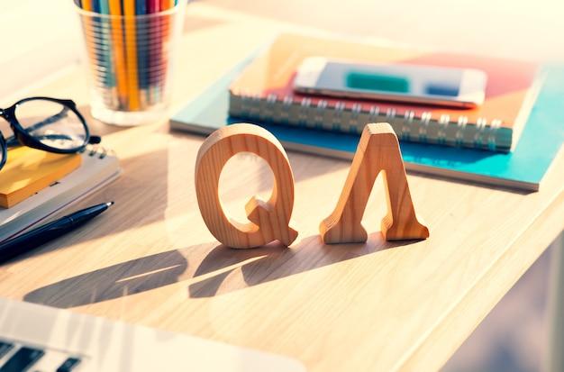 Fragen und antworten holzbuchstaben auf dem tisch