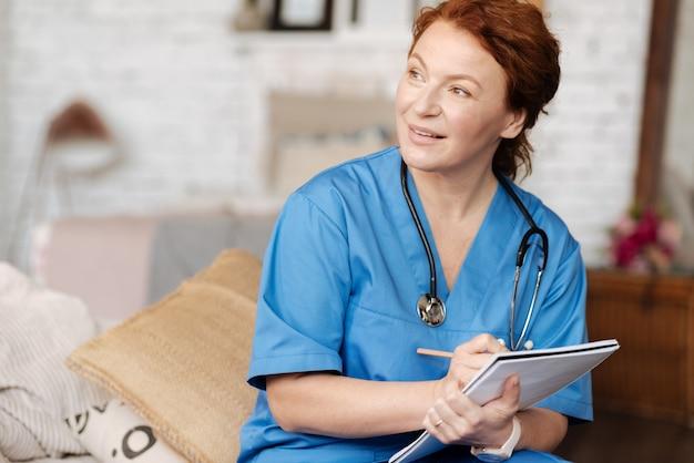 Fragen zum verständnis. erfolgreiche großartige lokale therapeutin, die die patientin zu hause besucht und eine konsultation durchführt, während sie wichtige daten in ihr tagebuch schreibt
