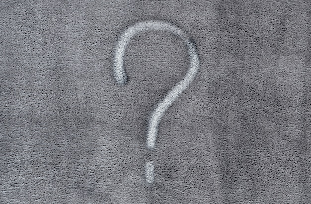 Fragezeichen auf grauem gewebebeschaffenheitshintergrund