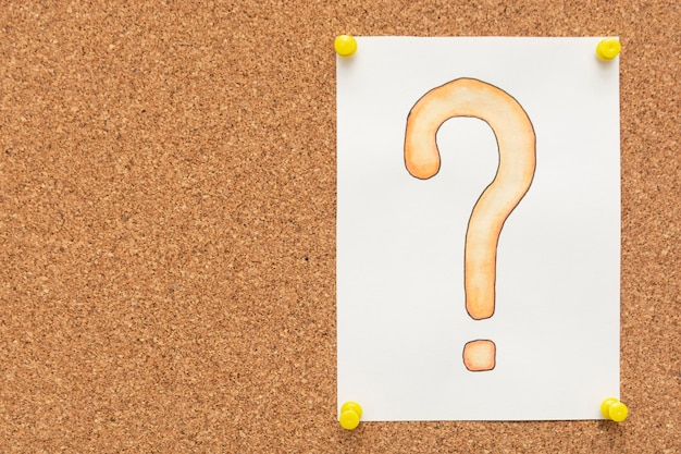 Fragezeichen gezeichnet auf das weißbuch, angeheftet auf korkenbrett