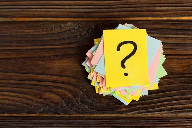 Fragezeichen-papierhaufen auf holztisch