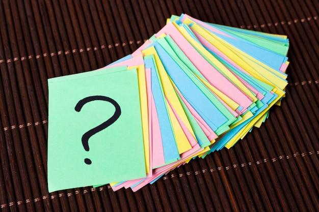 Fragezeichen-papierhaufen auf tabellenkonzept für verwirrung