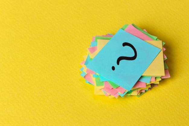 Fragezeichenpapierhaufen auf gelbem hintergrund
