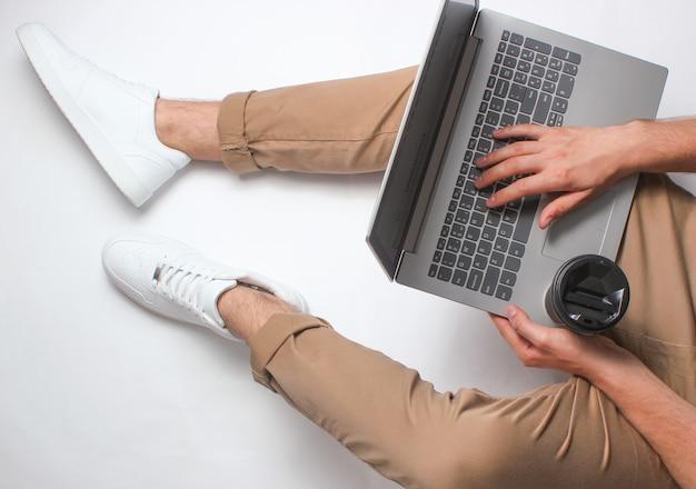 Fragment der männlichen beine in den beigen hosen und in den weißen turnschuhen, die auf weiß sitzen. mann mit modernem laptop. online-arbeiter, freiberuflich tätig, zu hause arbeiten, mann arbeiten. draufsicht