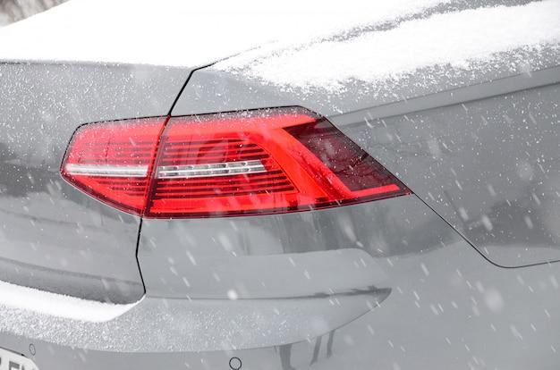 Fragment des autos unter einer schneeschicht nach starkem schneefall. die karosserie des autos ist mit weißem schnee bedeckt