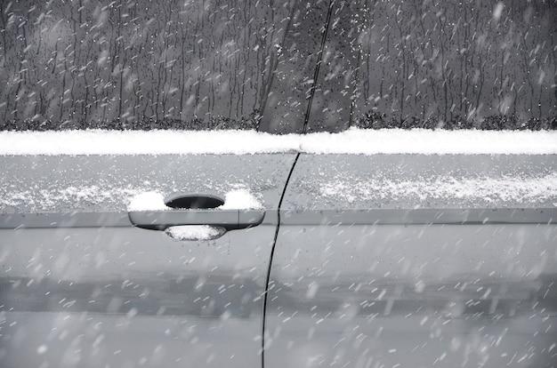 Fragment des autos unter einer schneeschicht nach starkem schneefall.