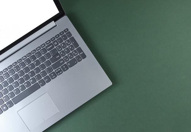 Fragment des laptops mit einem weißen bildschirm auf einem grünen tisch.