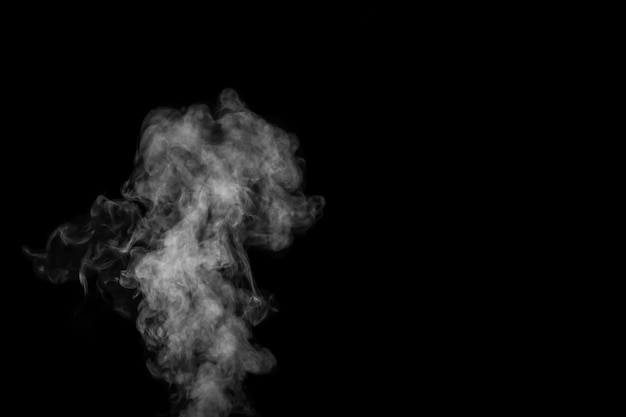 Fragment des weißen heißen lockigen dampfrauches lokalisiert auf einem schwarzen hintergrund, nahaufnahme. erstellen sie mystische halloween-fotos. abstrakter hintergrund, gestaltungselement