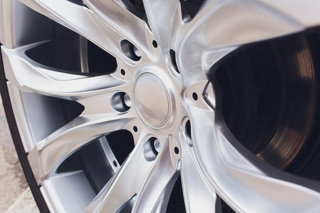 Fragment des weißen modernen autos mit rad auf stahlscheibe, nahaufnahmefoto.