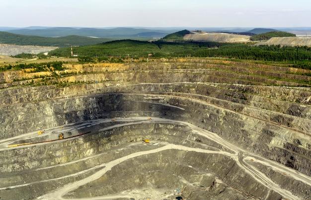 Fragment einer riesigen bergbaukarriere mit arbeitenden baggern, muldenkippern und anderer steinbruchausrüstung