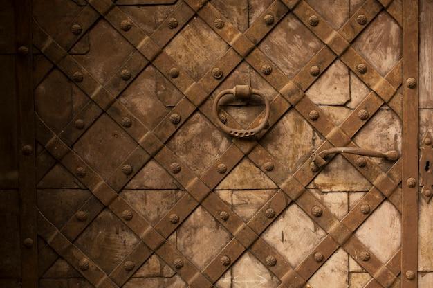 Fragment einer rostigen holztür mit metallelementen und griff