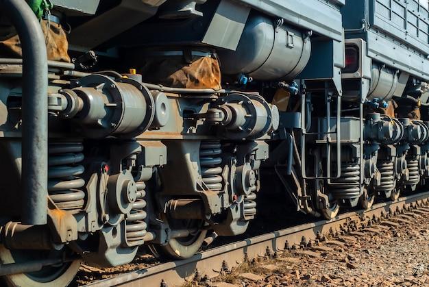Fragment einer sonnenbeschienenen modernen lokomotive auf einem gleis mit lkw-rahmen, die sich in die perspektive erstrecken