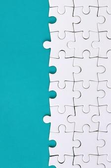 Fragment eines gefalteten weißen puzzles auf dem hintergrund