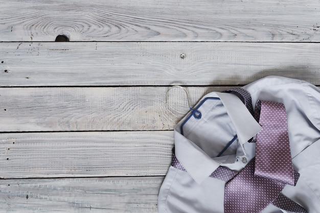 Fragment eines herrenhemdes mit krawatte auf einem kleiderbügel auf einer holzbemalten oberfläche. die pastellfarben