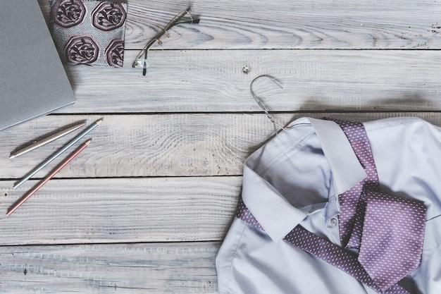 Fragment eines herrenhemdes mit krawatte auf einem kleiderbügel und tagebuch auf einer holzbemalten oberfläche. die pastellfarben