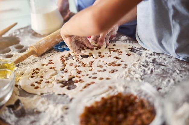 Fragmentfoto von talentierten bäckern, die kekse mit rosinen backen