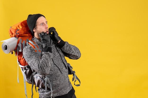 Fragte männlicher anhalter mit lederhandschuhen und rucksack