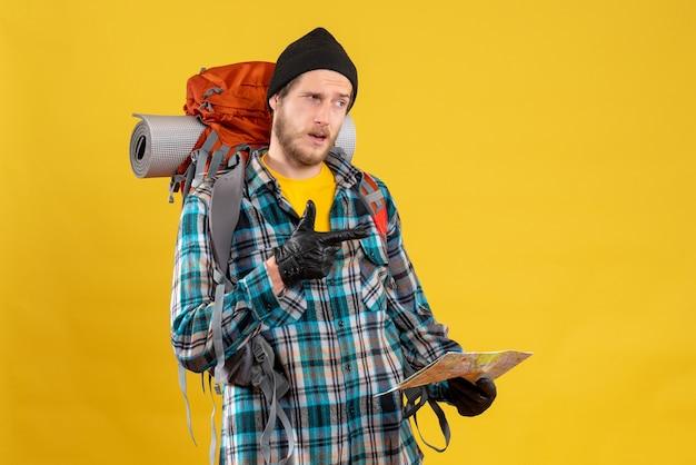 Fragte sich ein junger wanderer mit lederhandschuhen und rucksack, der eine karte hielt, die auf etwas zeigte?