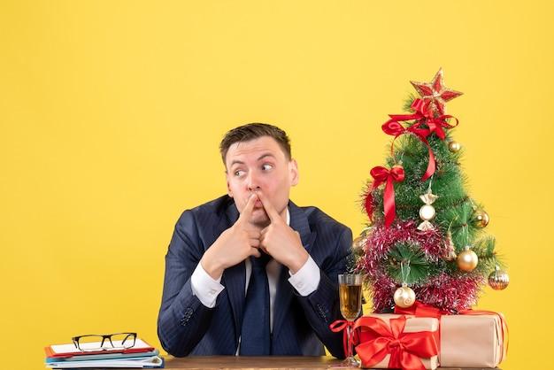 Fragte sich ein mann, der am tisch in der nähe des weihnachtsbaums saß und auf gelb präsentiert