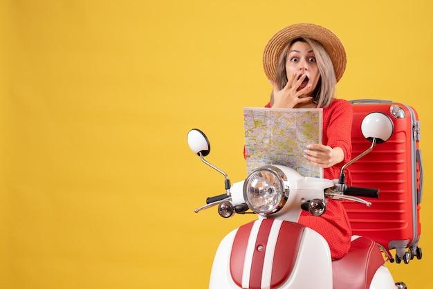 Fragte sich hübsches mädchen auf moped mit rotem koffer mit karte holding