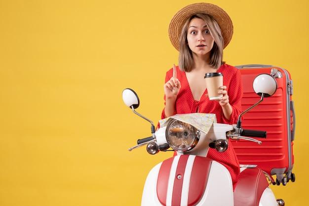 Fragte sich junge dame im roten kleid, die eine kaffeetasse in der nähe des mopeds hielt