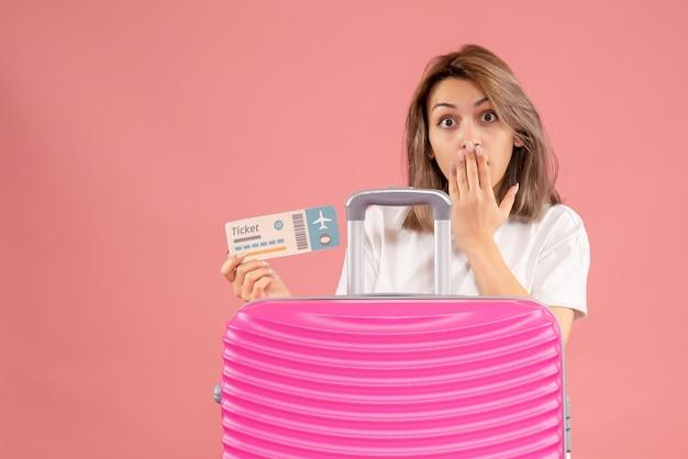 Fragte sich junge frau mit ticket hinter rosa koffer behind