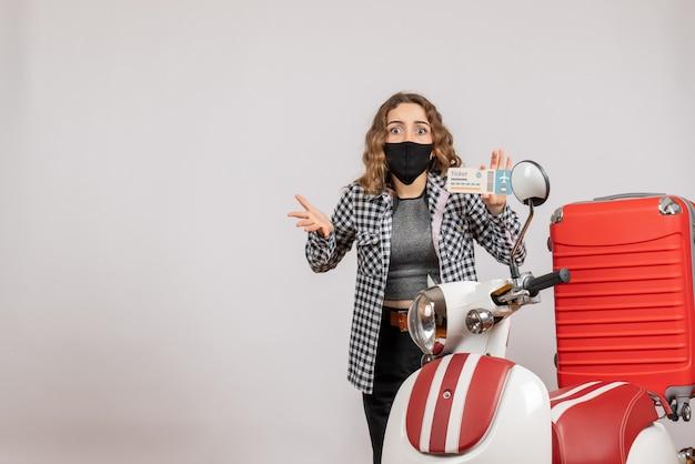 Fragte sich junges mädchen mit maske, das ein ticket in der nähe des mopeds mit koffer hält