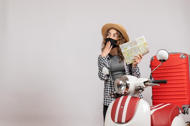Fragte sich junges mädchen mit schwarzer maske, das eine karte in der nähe des roten mopeds hielt